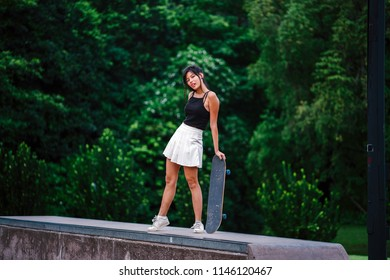 Portrait of a young, cute and attractive Chinese Asian millenial skater girl posing with her skateboard in a park. She is dressed in sporty attire and is smiling as she strikes a pose against trees.