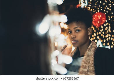 Portrait of young cute curly afro american girl surrounded by night city New Year or Christmas lights, garlands and decoration, she is vaping electronic cigarette, with copy space for text or logo