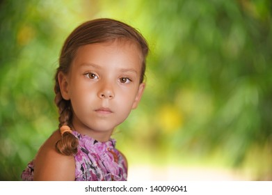 portrait of young cute girl in dress, against background of summer green park