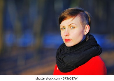 Portrait of young cute girl with a stylish haircut in a red coat and black scarf at the neck, posing in the bright sun on a blurred background of trees in the Park, closeup.
