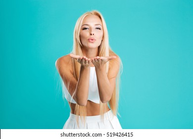 Portrait of a young cute woman blowing kiss at camera isolated on the blue background