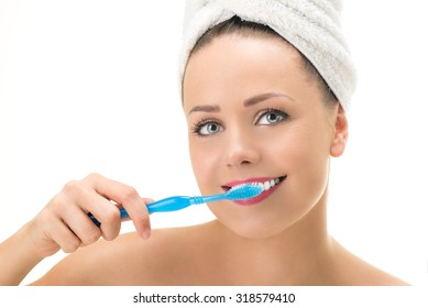 Portrait of Young cute woman brushing her teeth. Looking at camera. Close-up.