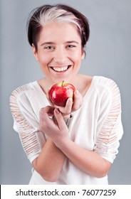 Portrait of young cute woman holding red apple and smiling