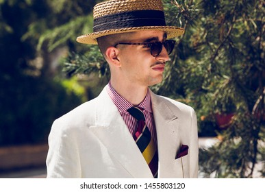 Portrait of a young dandy wearing a tie, a red pocket handkerchief and a straw boater hat, in front of greeneries
