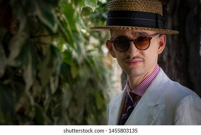 Portrait of a young dandy wearing a tie and a straw boater hat, in front of greeneries