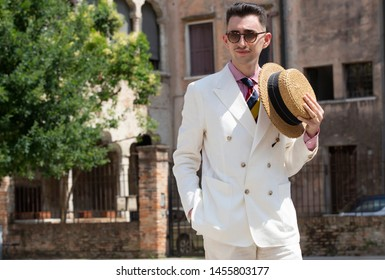 Portrait of a young dandy wearing a tie and a straw boater hat, in front of an old building in the streets of an Italian town
