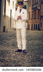 Portrait of a young dandy wearing a tie and a straw boater hat, in the streets of an Italian town