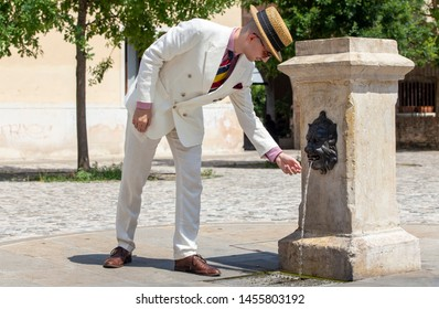 Portrait of a young dandy wearing a tie and a straw boater hat, in front of an old fountain in the streets of an Italian town