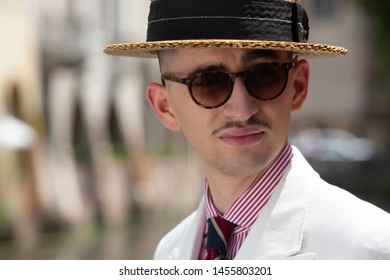 Portrait of a young dandy wearing a tie and a straw boater hat, in front of a river in the streets of an Italian town