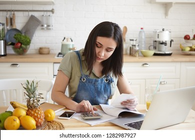 Portrait of young dark haired female wearing casual clothes at home, having focused concentrated look while calculating her debts for rent in kitchen, making notes, surrounded with papers and gadgets
