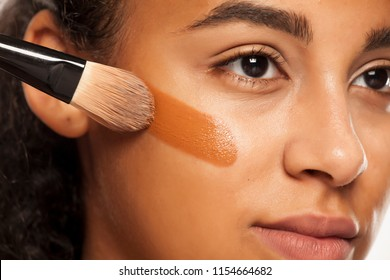 portrait of a young dark-skinned woman applying liquid makeup base with brush on her face on a white background
