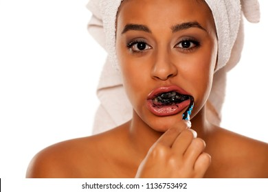 portrait of a young dark-skinned woman brushing her teeth with black toothpaste on a white background