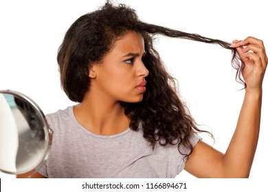 portrait of young dark-skinned woman with hair splitting problem on white background