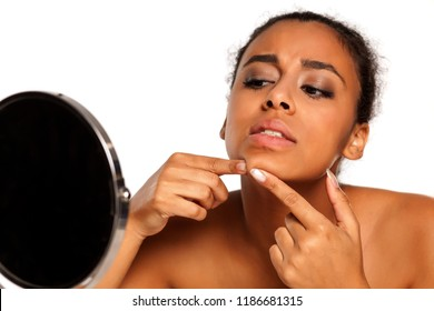 portrait of young dark-skinned woman squeeze a pimple on white background