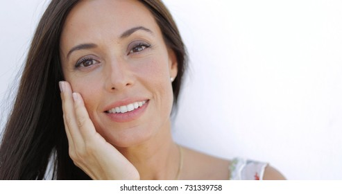 Portrait of young delightful model holding hand on face and looking gently at camera smiling slightly on white background.