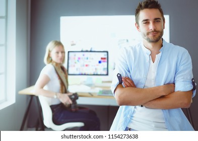 Portrait of young designer in front of laptop and computer while working. Assistant using her mobile at background.