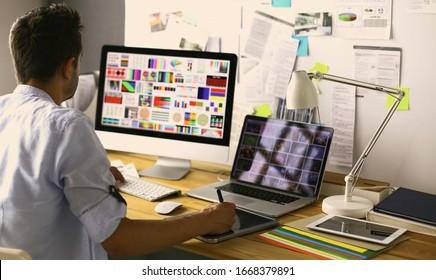 Porträt von jungen Designern, die im Grafikstudio vor Laptop und Computer sitzen, während sie online arbeiten.