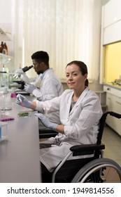 Portrait d'un jeune chimiste handicapé regardant la caméra pendant qu'il travaillait à la table dans le laboratoire