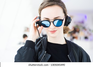 Portrait of a young dj with  red hair with blue sunglasses, leather jacket and dj headset,millenials theme.