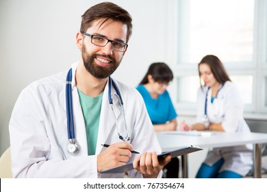 Portrait of a young doctor in a clinic with colleagues on the background
