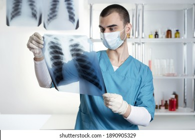 Portrait of a young doctor looking at x-ray rib cage, lungs, thorax. Lifestyle outdoor scene