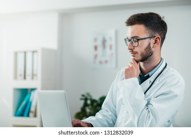 Portrait of Young Doctor on the Job working on laptop. Volunteer at the hospital gains practical knowledge in treating disease