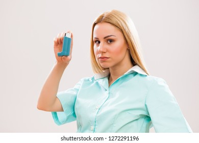 Portrait of young doctor who is holding inhaler.