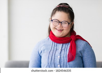 Portrait of a young down syndrome girl wearing eyeglasses in beautiful and colorful clothes looking at camera with a self-confident and wildly open smile with happiness. Idea for happy disabled kid.