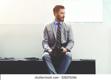 Portrait of a young dreamy male managing director in luxury suit resting after work on his digital tablet, successful man ceo thinking of new ideas while sitting with touch pad in corporation office