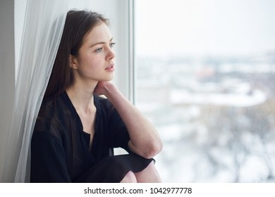 portrait of a young dreamy woman sitting on the window sill