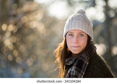 Portrait of a young Dutch woman in winter woods, while wearing a woolen cap and with beautiful bokeh and rimlight in woods near Breda, the Netherlands