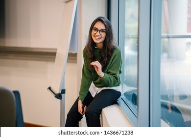 Portrait of a young, educated, confident and intelligent-looking Indian Asian teacher woman smiling as she sits in a seminar room by the window during the day in a preppy outfit.