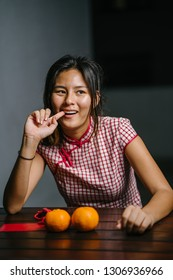 Portrait of a young, elegant and beautiful Chinese Asian girl in a traditional Chinese qipao dress sits at a bench with a pair of oranges in front of her. She is looking mischievously at the camera.