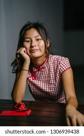 Portrait of a young, elegant and beautiful Chinese Asian girl in a traditional Chinese qipao dress sits at a bench. She is smiling and is talking to the camera casually.