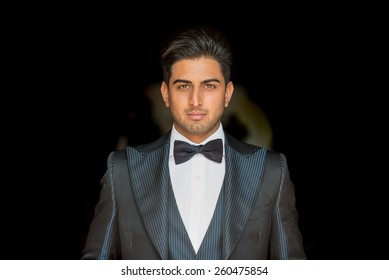 Portrait of young elegant indian groom on black background