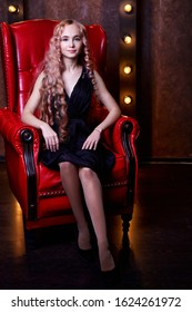 Portrait of young elegant tender blonde teenage girl wearing black dress with serious or pensive expression on red armchair in dark room. Caucasian female model with very length hair posing in studio