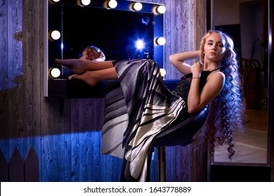 Portrait of young elegant tender blonde teenage girl in black dress in room near the mirror with flashlights. Caucasian female model with very long hair posing in studio. Actress after performance