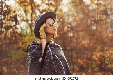 Portrait of a young, elegant woman looking away from the camera. Photogaph taken in autumn surrounding.