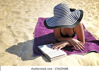 Portrait of a young elegant woman wearing a large black and white striped beach hat and a black bikini reading on the beach.