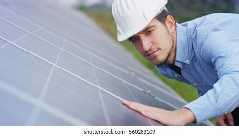 The portrait of a young engineer checks with his hand operation with sun,  cleanliness on field of photovoltaic solar panels. Concept: renewable energy, technology, electricity, service, green power.