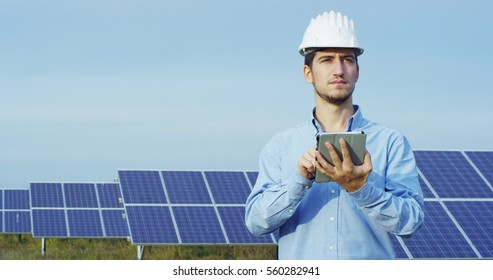 The portrait of a young engineer checks with tablet operation with sun,  cleanliness on field of photovoltaic solar panels. Concept: renewable energy, technology, electricity, service, green power.