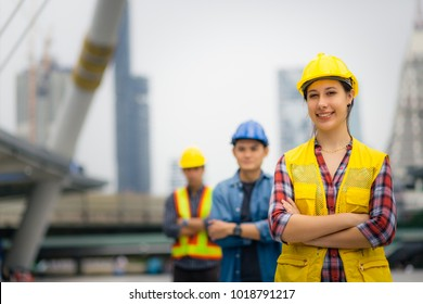 Portrait of young engineer girl, posing outdoor with team and construction on background