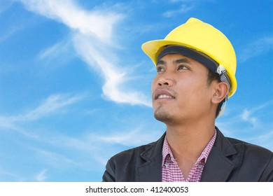 Portrait of young engineer on sky background