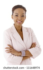 Portrait of young ethnic businesswoman smiling at camera confidently with arms crossed.
