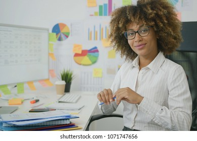 Portrait of young ethnic woman wearing elegant white shirts and eyeglasses sitting at working desk in office and smiling gently at camera.
