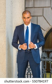 Portrait of Young European Businessman in New York. Wearing blue suit, white shirt, tie, Mixed Race French guy with shaved head stands outside office, serious, tensely thinking.