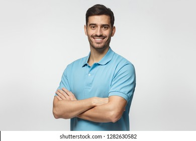 Portrait of young european caucasian man isolated on gray background, standing in blue polo shirt with crossed arms, smiling and  looking at camera