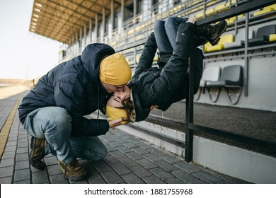 Portrait of young European couple man and woman in yellow hats and winter jacket having fun and hugging near yellow, gay stadium seats. Style, girlfriend, friend, date, love, wild, kiss.