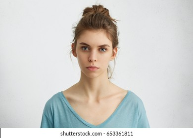 Portrait of young European female with healthy clean skin and blue eyes wearing casual top looking at camera with serious expression. Caucasian woman model with hair gathered in bunch posing indoors