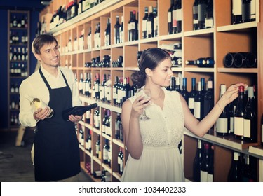 portrait of young european glad female customer tasting wine before purchasing